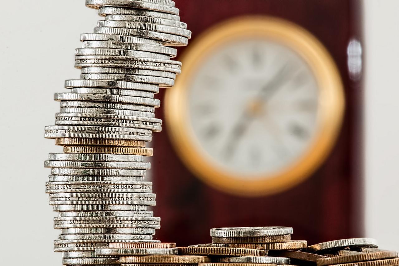 stos pieniędzy, w tle rozmyty zegar